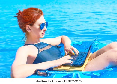 Beautiful young woman with on donuts and a desktop computer relaxing in the ocean.