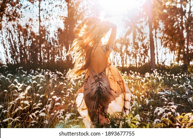 beautiful young woman on the field at sunset