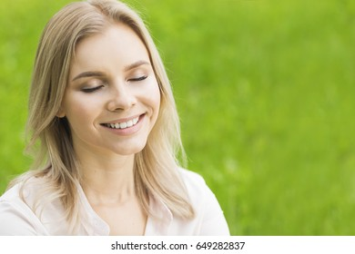 A beautiful young woman on grass enjoy nature smiling with closed eyes