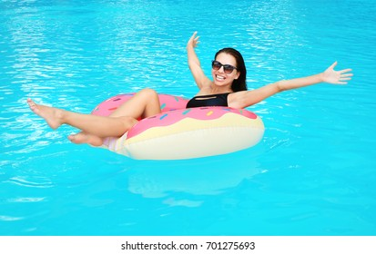 Beautiful young woman on inflatable donut in swimming pool