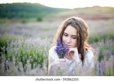 Beautiful young woman on lavander field with guitar