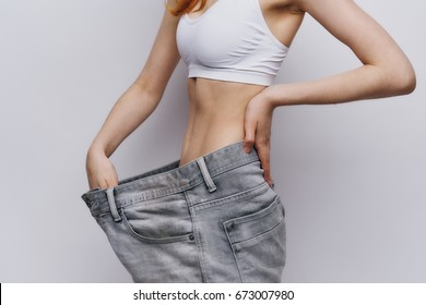 Beautiful young woman on a light background, lean. Diet, losing weight, success, progress.