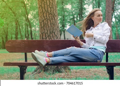 Beautiful young woman on the nature bench reading a book dreaming sun
