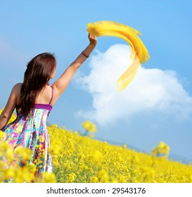 beautiful young woman on rapeseed field with yellow scarf