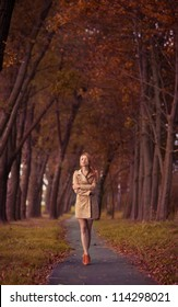 beautiful young woman on the road among the autumn trees