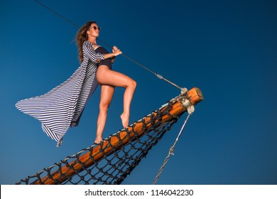 Beautiful young woman on a sailing boat  at sunset