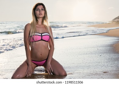 Beautiful young woman on a sandy ocean beach in a swimsuit at sunset