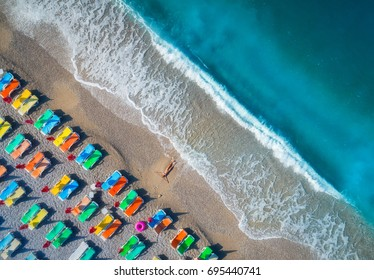 Beautiful young woman on the sea at sunrise in Oludeniz, Turkey. Aerial view of lying woman on the beach with colorful chaise-lounges. Top view from drone. Seascape with girl, azure water and waves