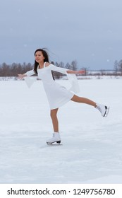 Beautiful young woman on skates in white dress outdoors at winter snow