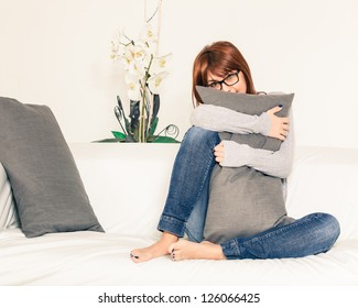 Beautiful Young Woman on the Sofa with a Pillow