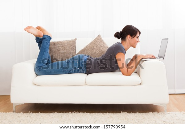 Beautiful Young Woman On A Sofa Working With A Laptop