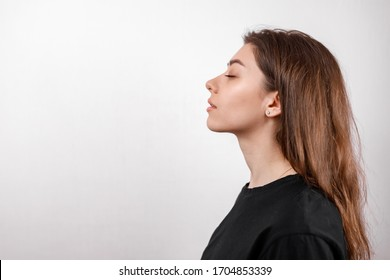 beautiful young woman on a white background stands in profile in a black shirt. copyspace. isolate