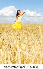 Beautiful young woman on the yellow wheat field
