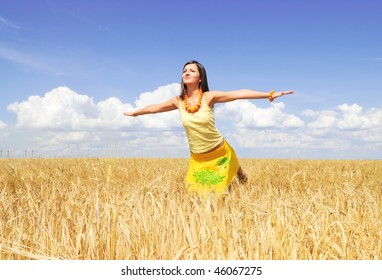 Beautiful young woman on a yellow wheat field
