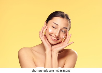 Beautiful young woman on a yellow background, cosmetic face cream.