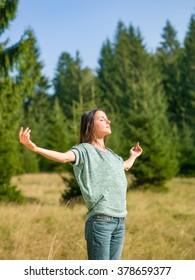 beautiful young woman with open arms enjoying sunny summer day in nature with trees