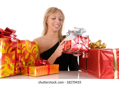 Beautiful young woman opening the colorful gifts. Merry christmas