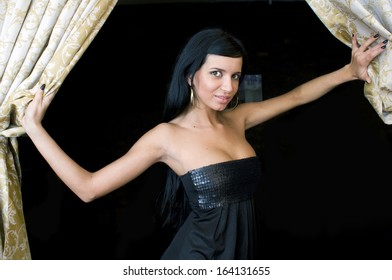 Beautiful young woman is opening the curtains