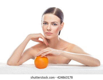 beautiful young woman with orange isolated on white background. Skin care and beauty.