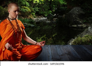 Beautiful young woman in orange robe sits in meditation on the background of the zen garden..Meditation is the best way to solve the most complex problems.
