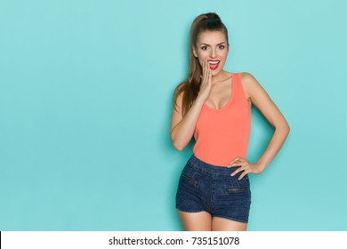 Beautiful young woman in orange tank top is holding hand on chin and talking. Three quarter length studio shot on turquoise background.