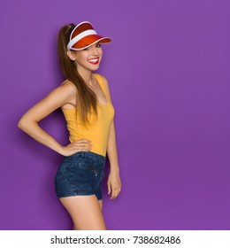 Beautiful young woman in orange tank top, transparent sun visor and jeans shorts is smiling and looking at camera. Three quarter length studio shot on purple background.