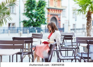 Beautiful young woman in an outdoor cafe writing in a notebook and planning her day in Vienna, Austria