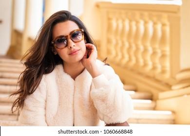 Beautiful young woman outdoor fashion portrait wearing sunglasses.