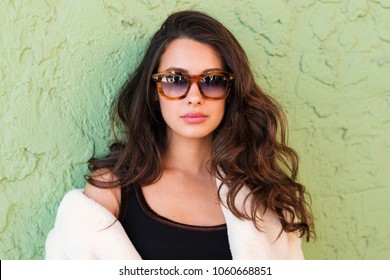 Beautiful young woman outdoor fashion portrait wearing sunglasses.