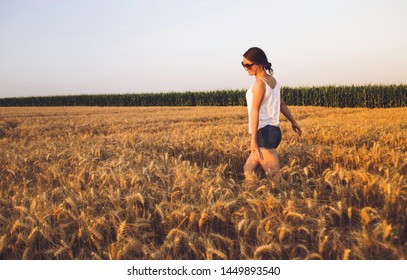 Beautiful Young Woman Outdoors Enjoying Nature in Wheat Field