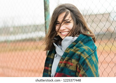 Beautiful young woman outdoors on windy day, smiling. No makeup, no retouch, natural lighting.