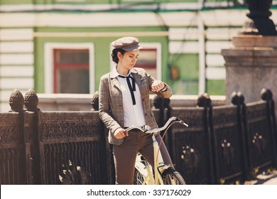 """Beautiful young woman outdoors riding vintage bicycle, looking at wrist watch. Girl wears british style """"tweed ride"""", brown plaid jacket and flat cap"""