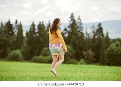 Beautiful Young Woman Outdoors. Smiling Girl in Green Grass.