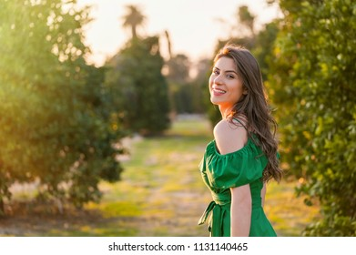Beautiful young woman, outdoors at sunset in a orange orchard, looking at camera and smiling gently . Healthy lifestyle concept, skin and hair care concept.