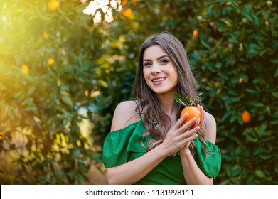 Beautiful young woman, outdoors at sunset in a orange orchard, looking at camera and smiling, holding an orange fruit. Healthy lifestyle concept, skin and hair care concept.