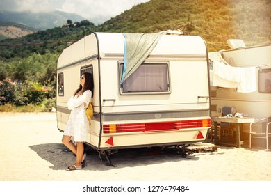 Beautiful young woman outside the camper van on a summer day beach mountains in background, Albania