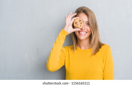 Beautiful young woman over grunge grey wall eating chocolate chip cooky with a happy face standing and smiling with a confident smile showing teeth