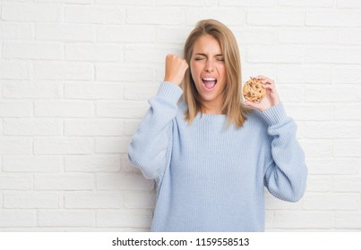 Beautiful young woman over white brick wall eating chocolate chip cooky annoyed and frustrated shouting with anger, crazy and yelling with raised hand, anger concept