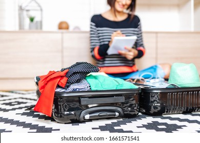 Beautiful young woman packing her stuff into a big suitcase. Traveling preparation concept.