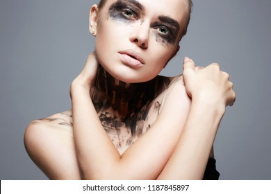 Beautiful Young woman with Paint Face. paint over a face and Body. Halloween style Girl in Black Paint