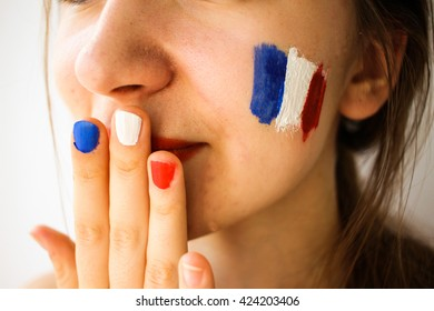 Beautiful young woman with painted french flag on face, hand & manicure, olympic games supporter
