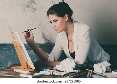 beautiful young woman painter in her studio, selective focus