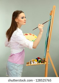 beautiful young woman painter at work, on grey background