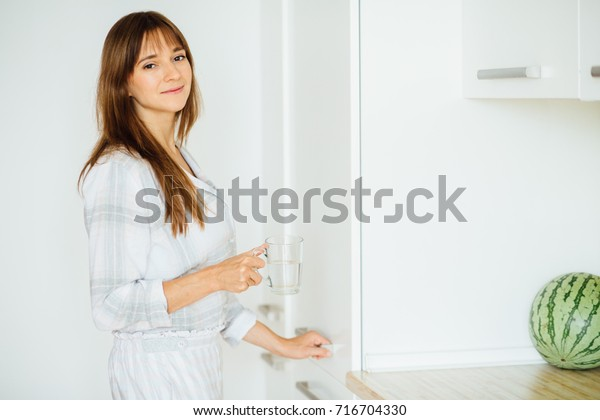 Beautiful young woman in pajamas with glass of water in kitchen