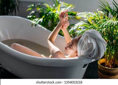 Beautiful young woman pampering her body in water, taking bath with mineral oils in relaxing atmosphere of hotel spa zone at sunny morning