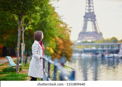 Beautiful young woman in Paris looking at the Eiffel tower and the Seine on a bright fall day. Tourism and vacation in France at autumn season