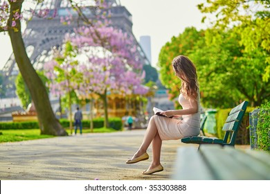 Beautiful young woman in Paris, near the Eiffel tower on a nice and sunny spring day, reading on the bench outdoors