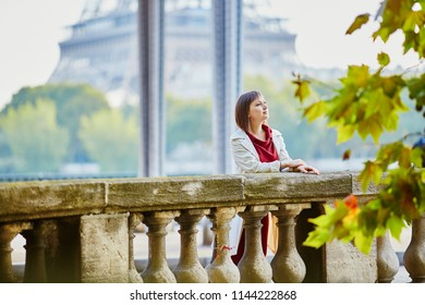 Beautiful young woman in Paris on Bir-Hakeim bridge with view to Eiffel tower on a fall or spring day. Tourism and vacation in France