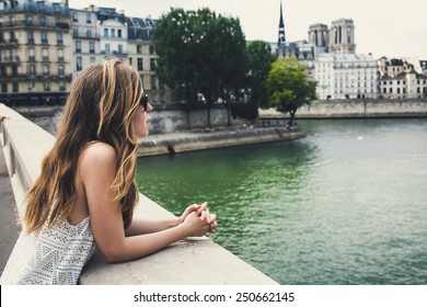 Beautiful young woman in Paris on holidays in France staying near Seine river while walking on Champs-Elysees, Paris, France