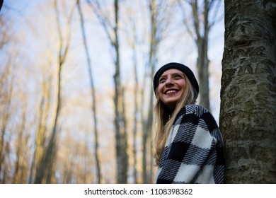 Beautiful young woman in park, between trees, with long and blonde hair (selective focus)